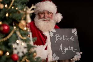 santa claus with a believe again sign